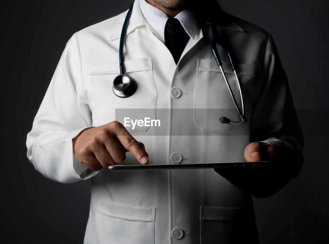Midsection Of Doctor Holding Digital Tablet Over Black Background