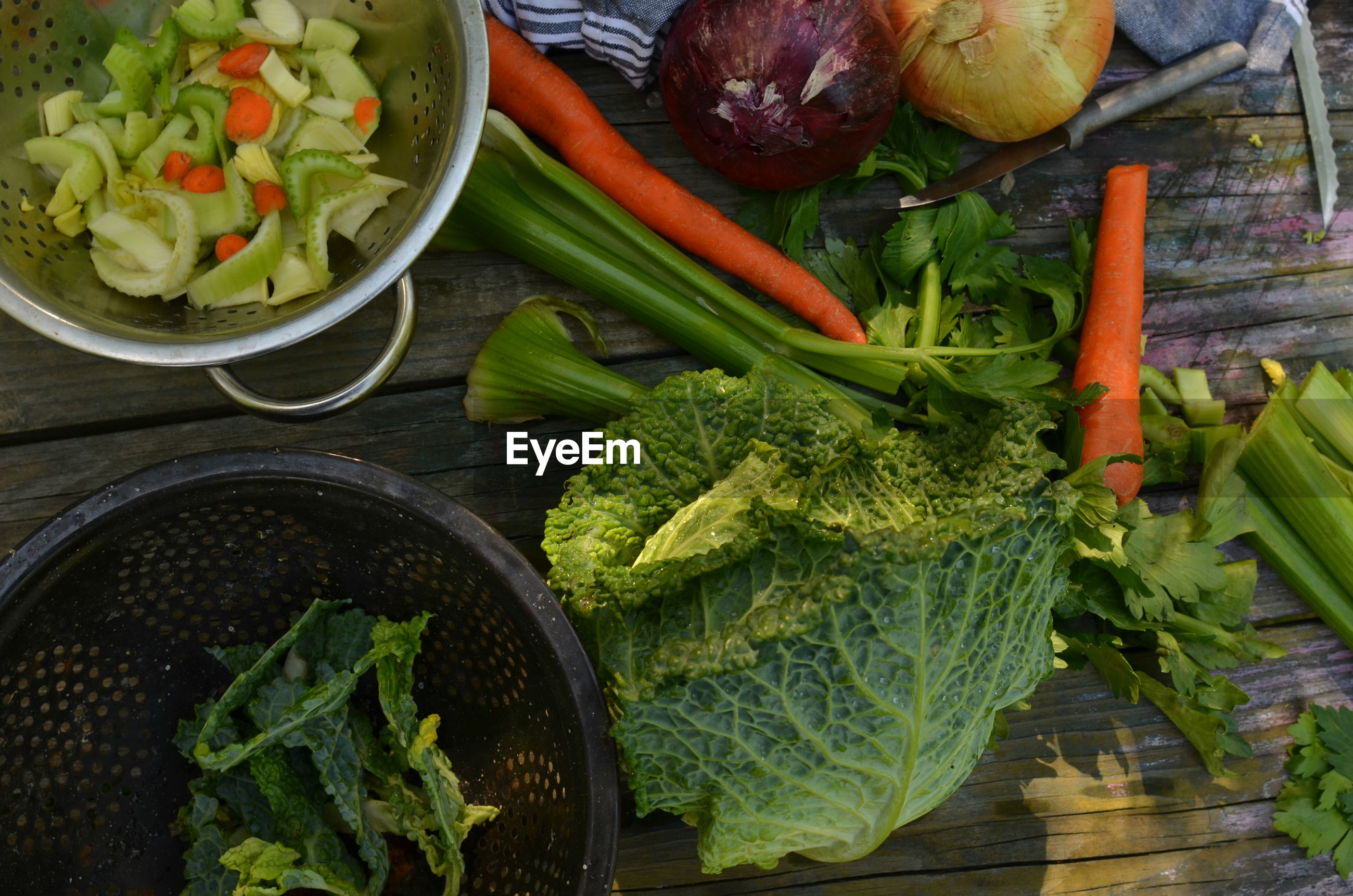 Overhead view of savoy cabbage, celery, carrots, collanders