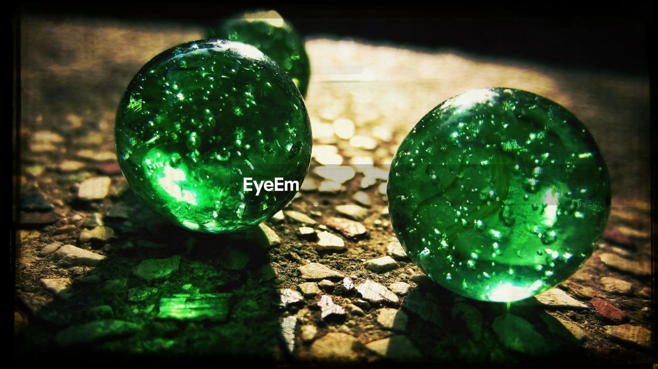 Close-Up Of Green Marbles On Ground