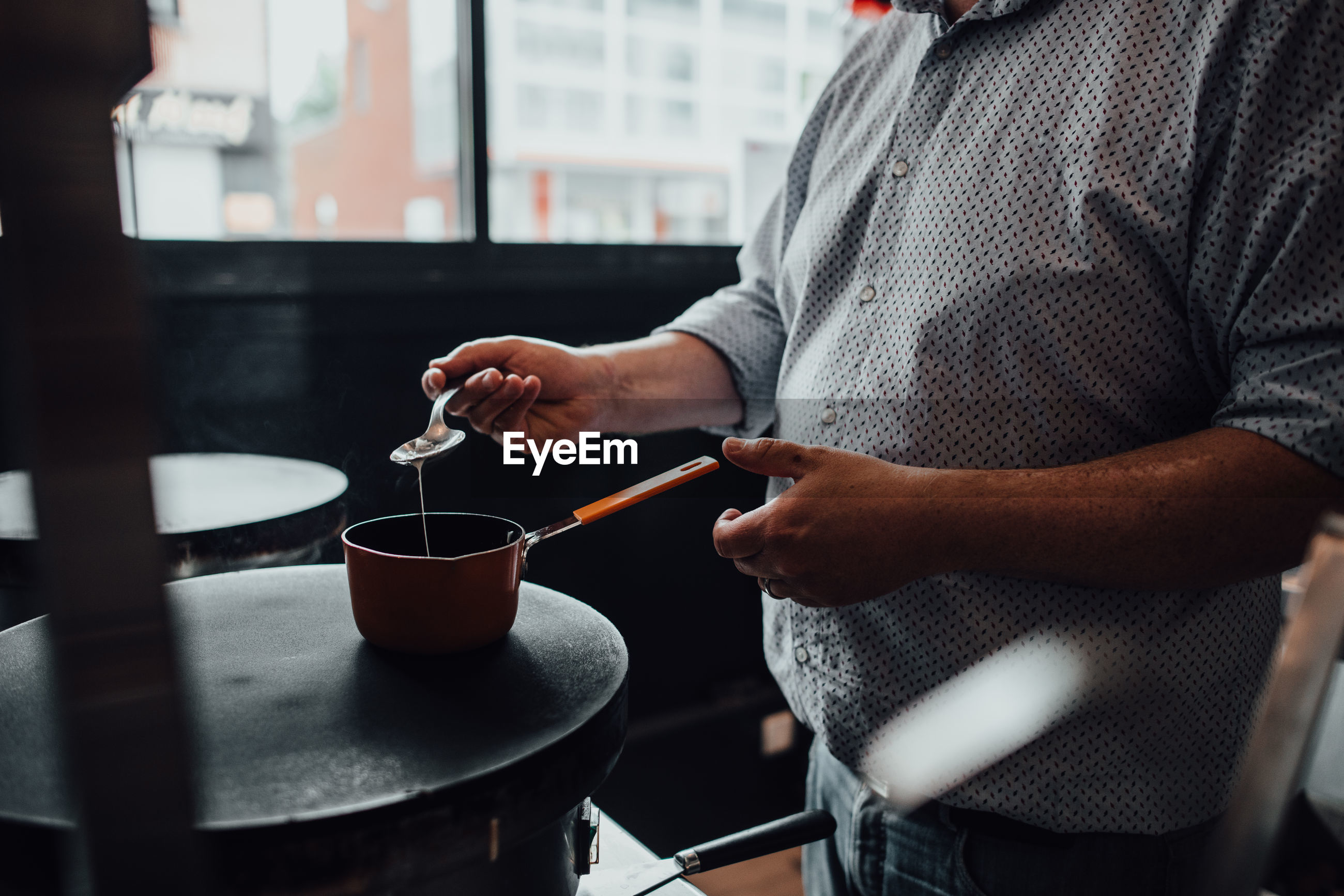 MIDSECTION OF MAN HOLDING COFFEE WHILE STANDING AT KITCHEN