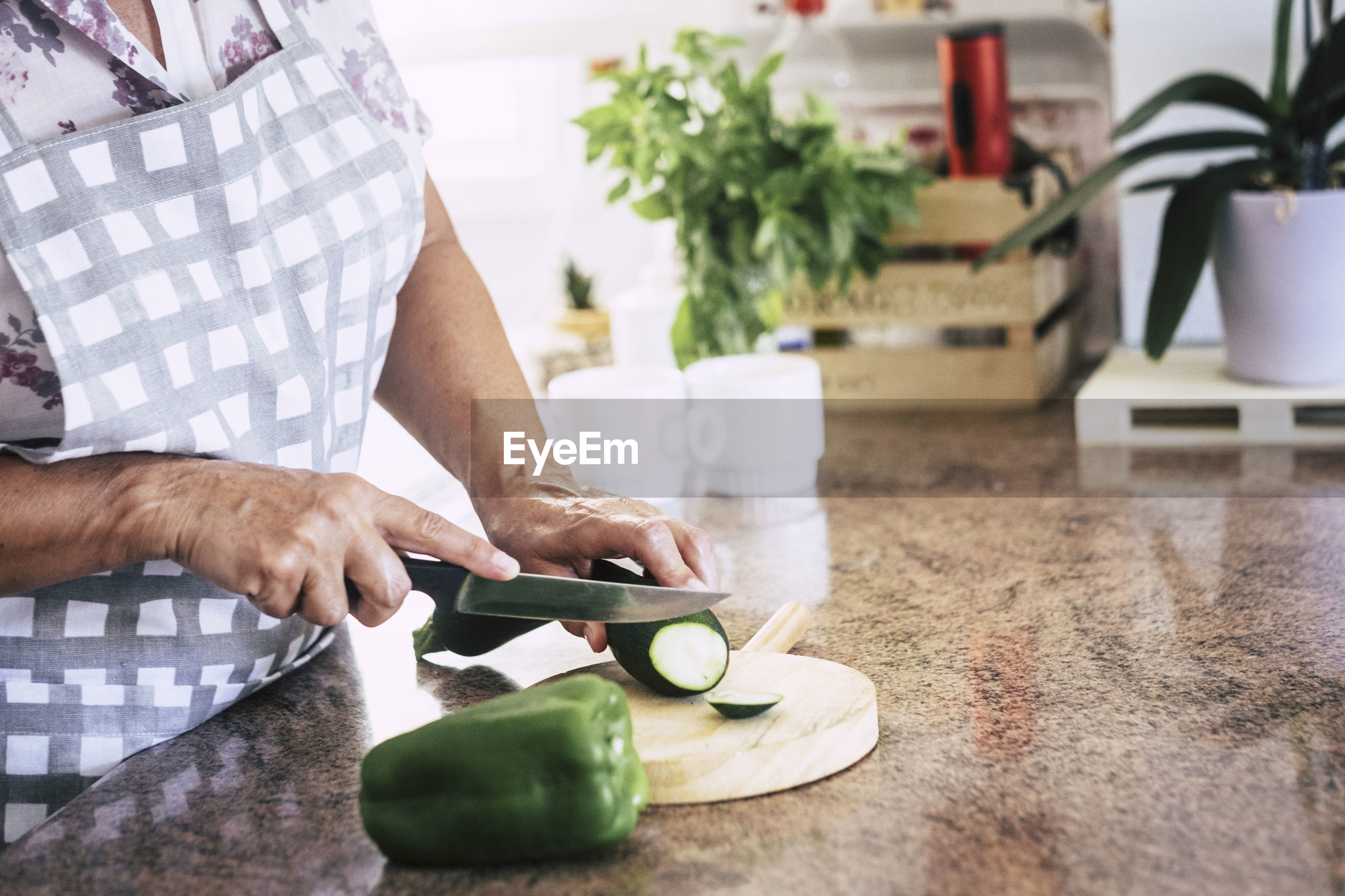 Midsection of woman cutting vegetable in kitchen at home