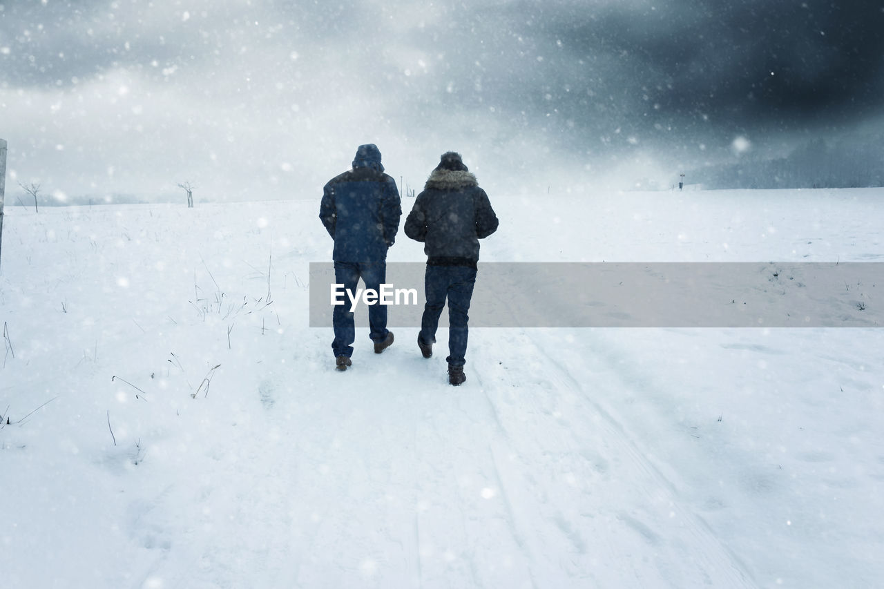 Rear view of people walking on snow during snowfall
