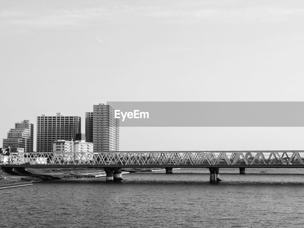 architecture, built structure, building exterior, bridge - man made structure, city, copy space, connection, skyscraper, water, outdoors, river, clear sky, waterfront, day, modern, no people, sky, travel destinations, nature, cityscape