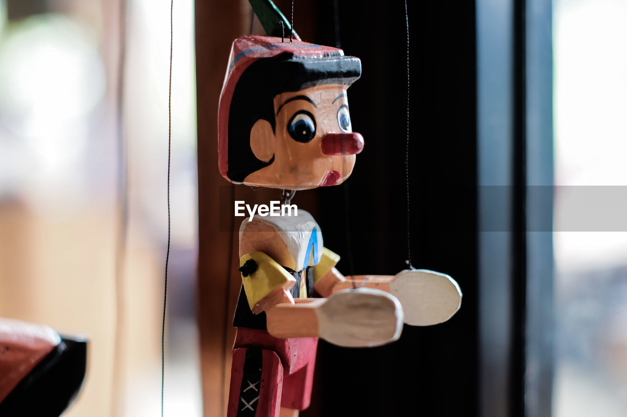 Close-up of toy hanging on window