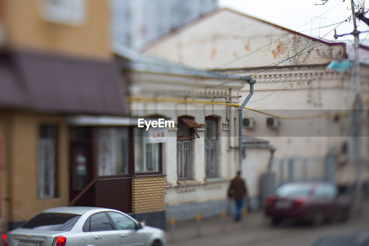 building exterior, car, motor vehicle, built structure, architecture, mode of transportation, transportation, city, land vehicle, focus on foreground, day, incidental people, building, selective focus, outdoors, residential district, street, nature, travel