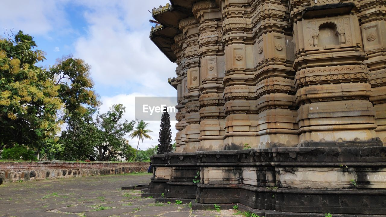 architecture, built structure, building exterior, sky, tree, day, history, religion, the past, nature, no people, cloud - sky, plant, place of worship, spirituality, building, low angle view, travel destinations, ancient, outdoors, architectural column, ancient civilization