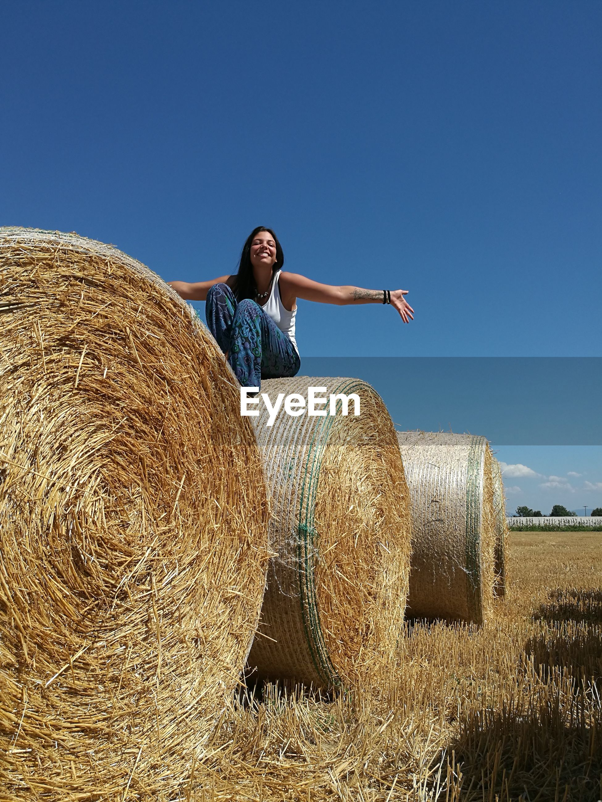 Low angle view of cheerful young woman sitting on hay bale against clear sky