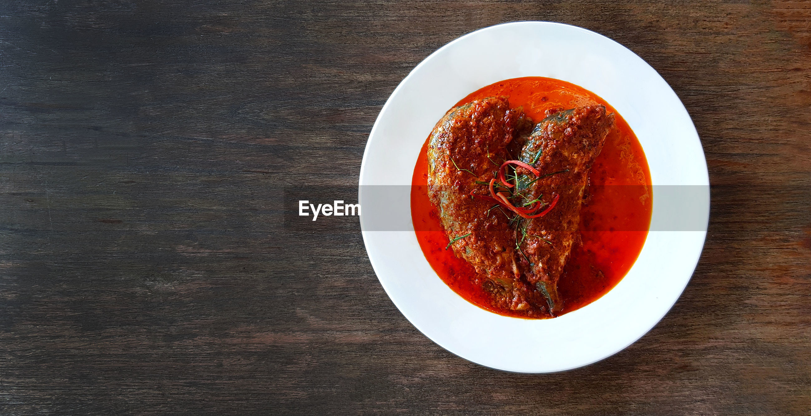High angle view of spicy red soup with fish served on table with copy space