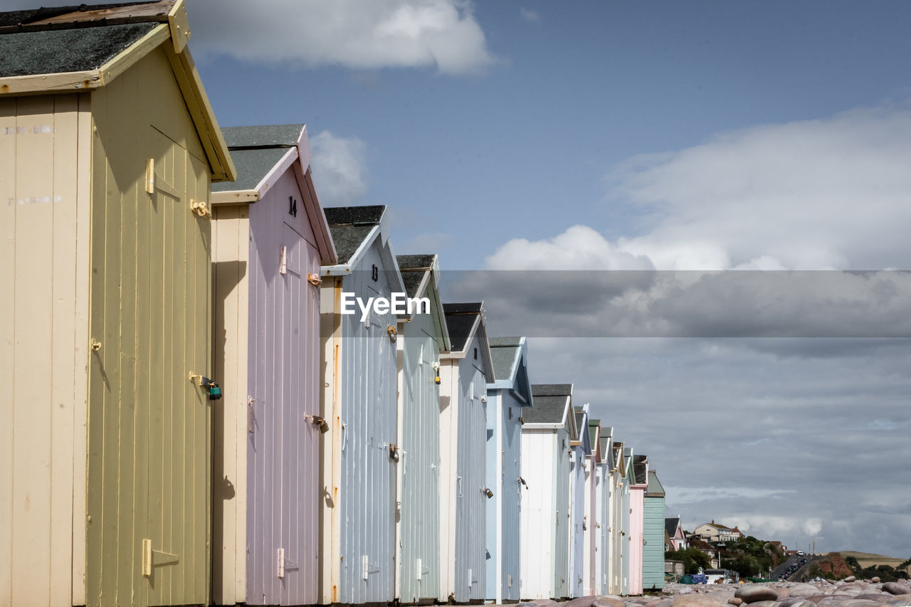 architecture, built structure, building exterior, sky, cloud - sky, day, building, nature, in a row, no people, outdoors, white color, residential district, house, beach hut, sunlight, low angle view, side by side, city, water