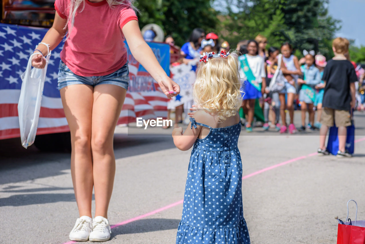 Low Section Of Young Woman Giving Candies To Girl On Street