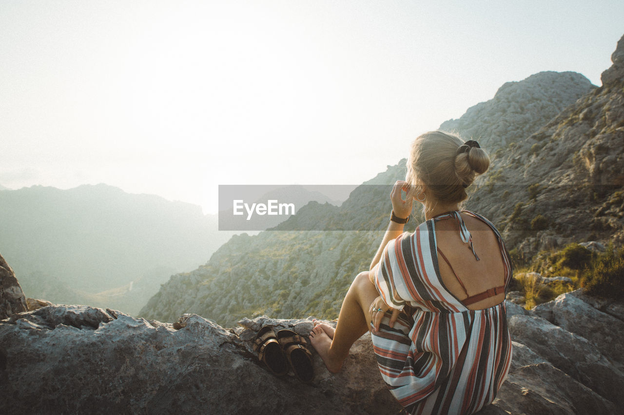 Rear View Of Young Woman Looking At Mountains Against Sky