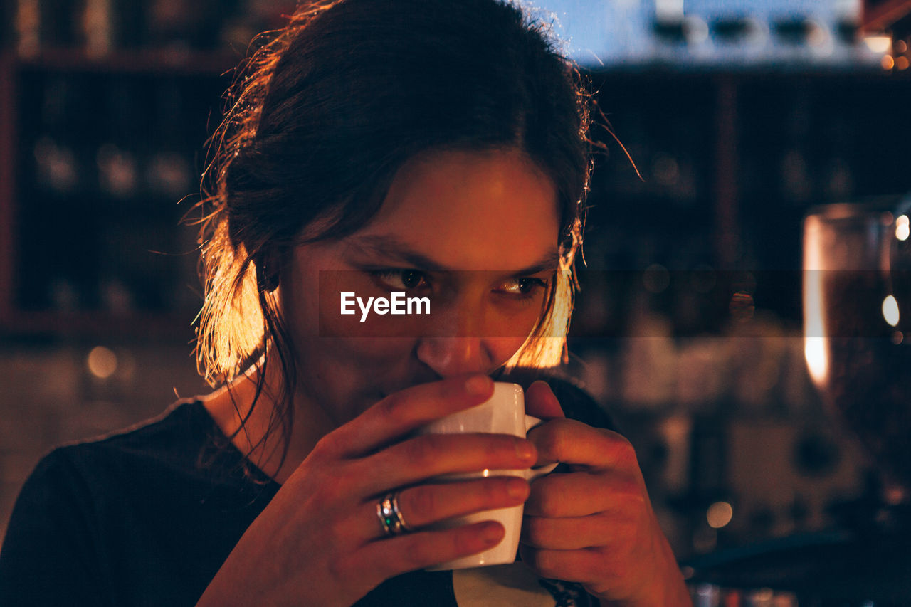 Close-Up Of Young Woman Drinking Coffee At Night