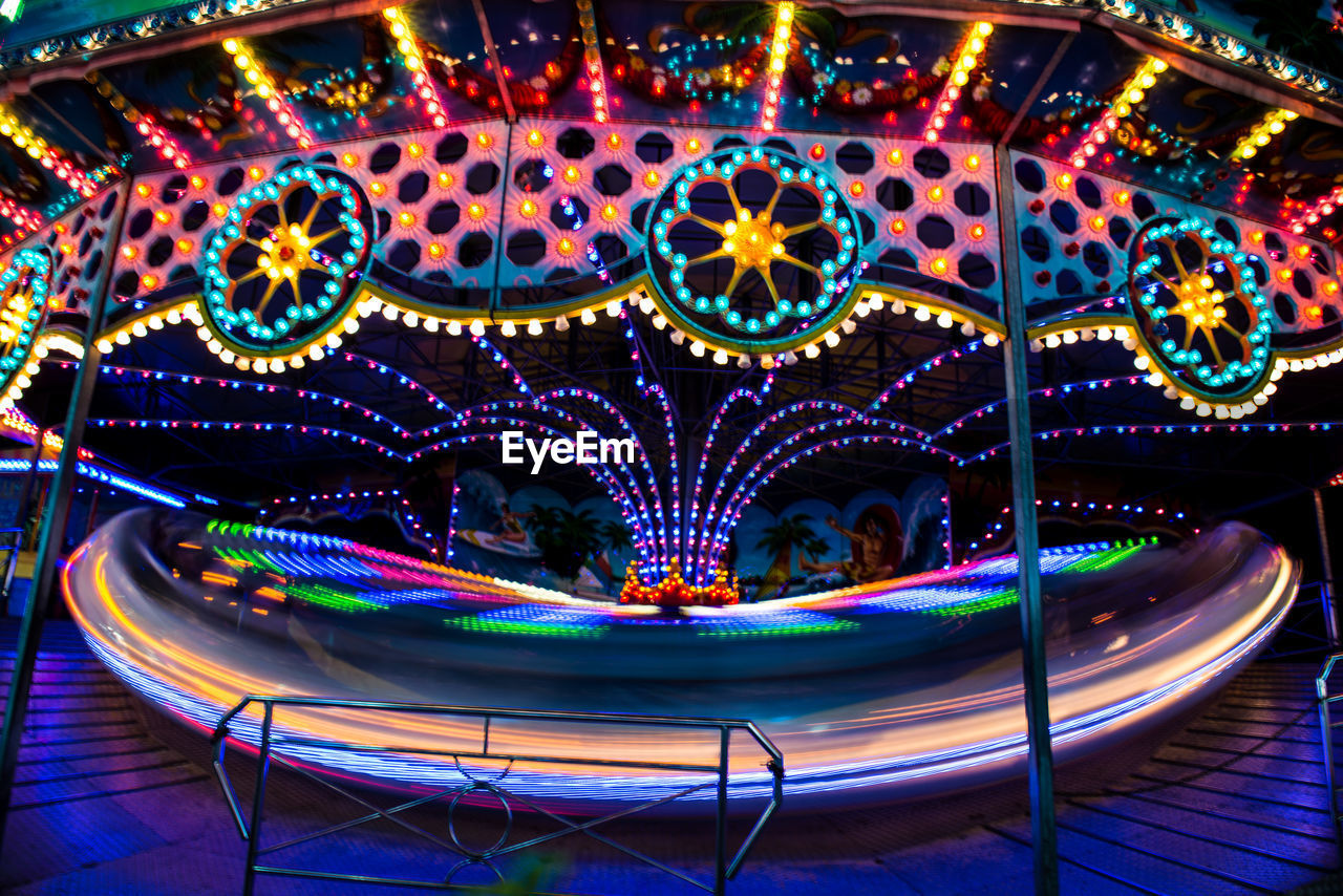 amusement park, amusement park ride, illuminated, night, carousel, arts culture and entertainment, blurred motion, motion, long exposure, lighting equipment, leisure activity, no people, glowing, outdoors, speed, multi colored, merry-go-round, light trail, ride, fairground