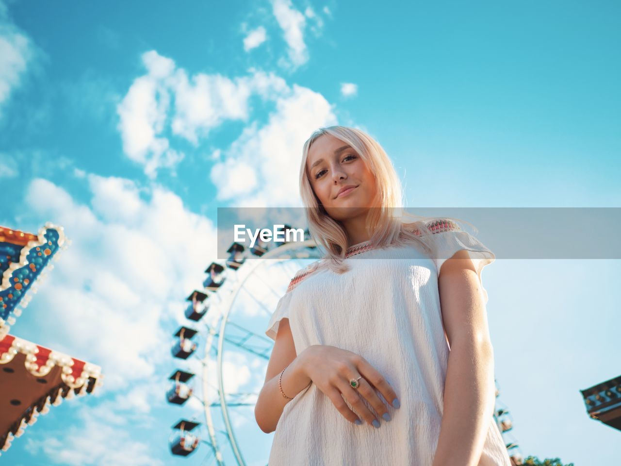 Portrait Of Smiling Young Woman In Amusement Park Against Sky