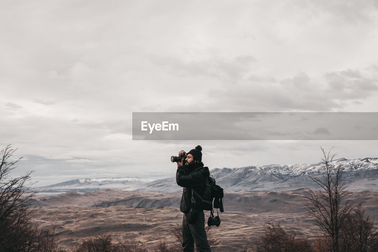 Man Photographing On Mountain Against Sky