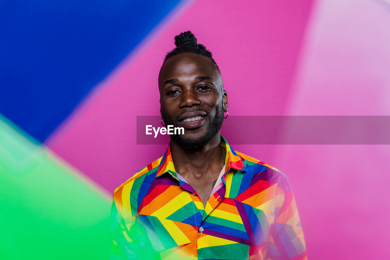 Portrait of smiling man against colored background
