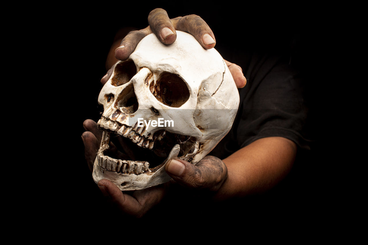Cropped image of hand holding skull against black background