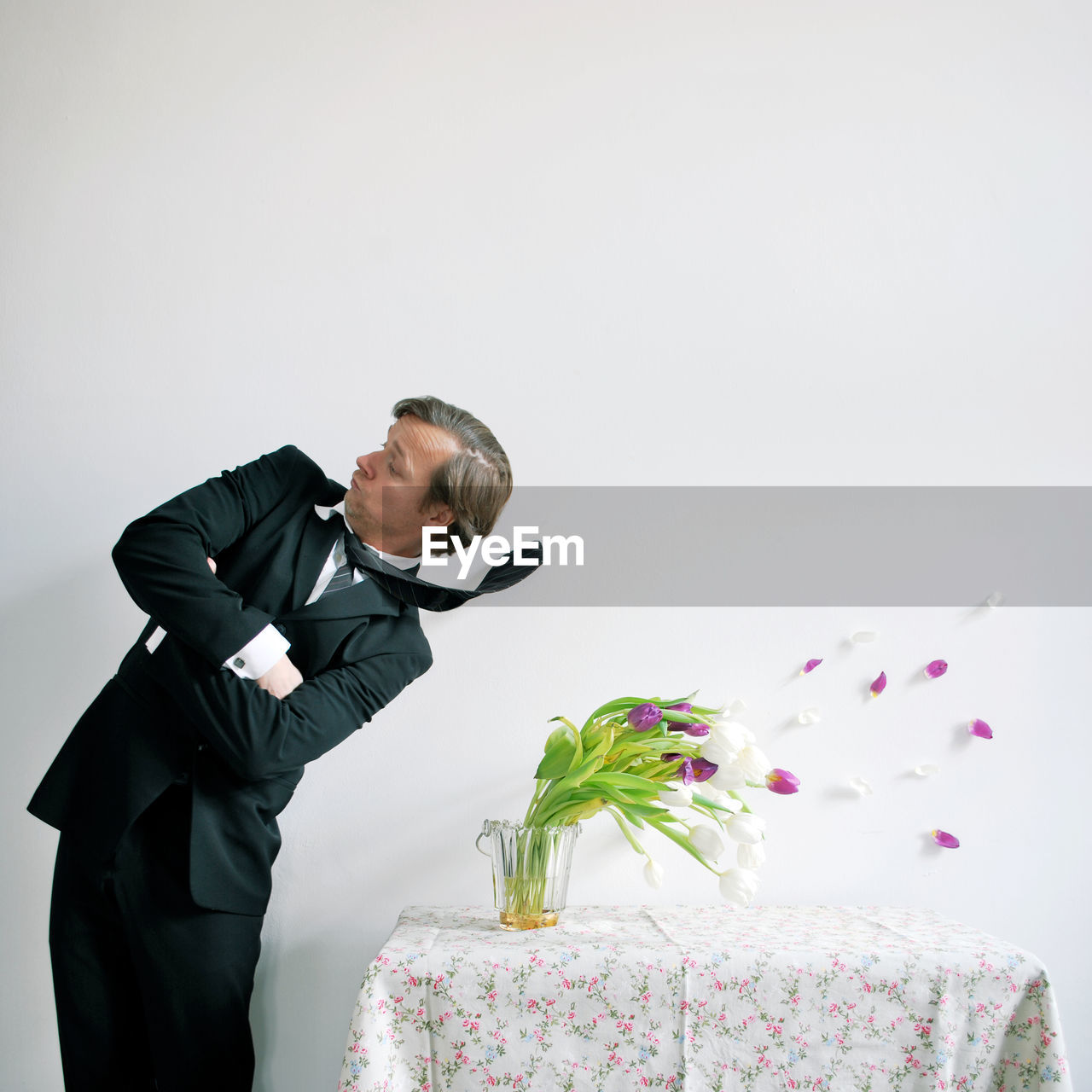 Man Standing By Flowers On Table Against White Background