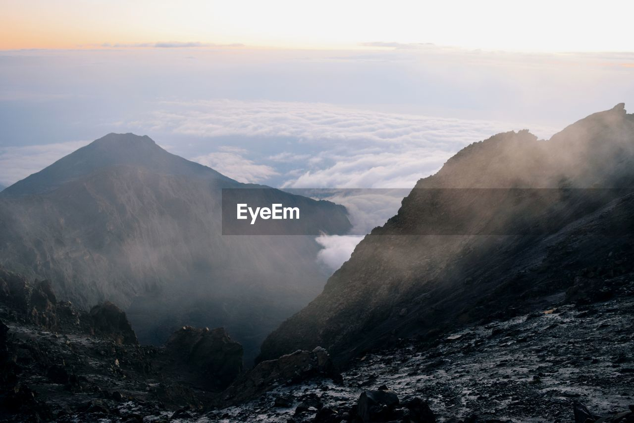 Scenic view of mountain range against sky, sunrise above the clouds, mount meru, tanzania