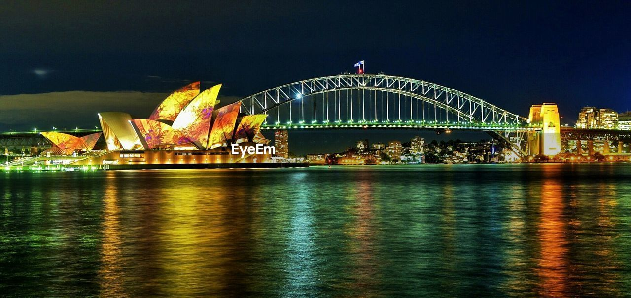 Illuminated Sydney Harbor Bridge And Opera House In City