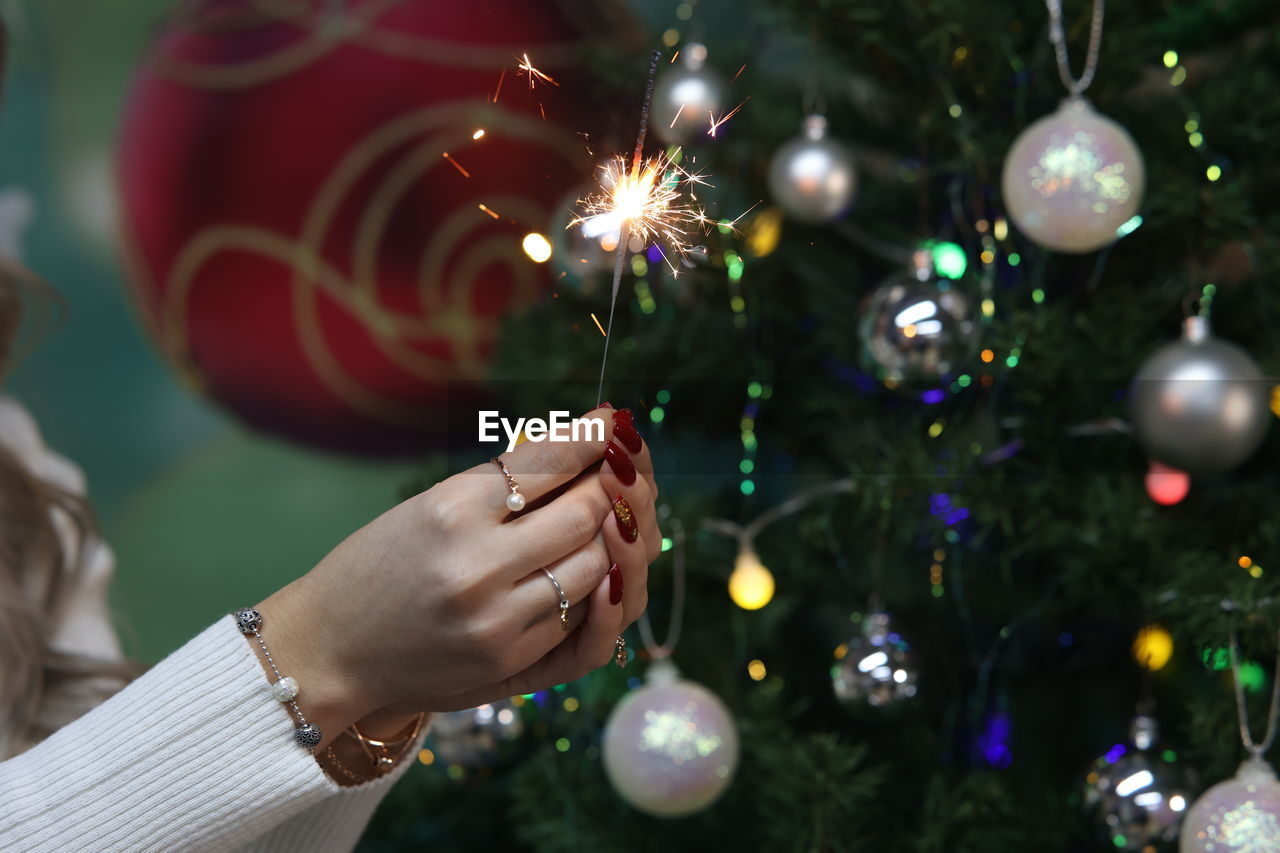 Cropped image of woman holding sparkler against christmas tree decoration