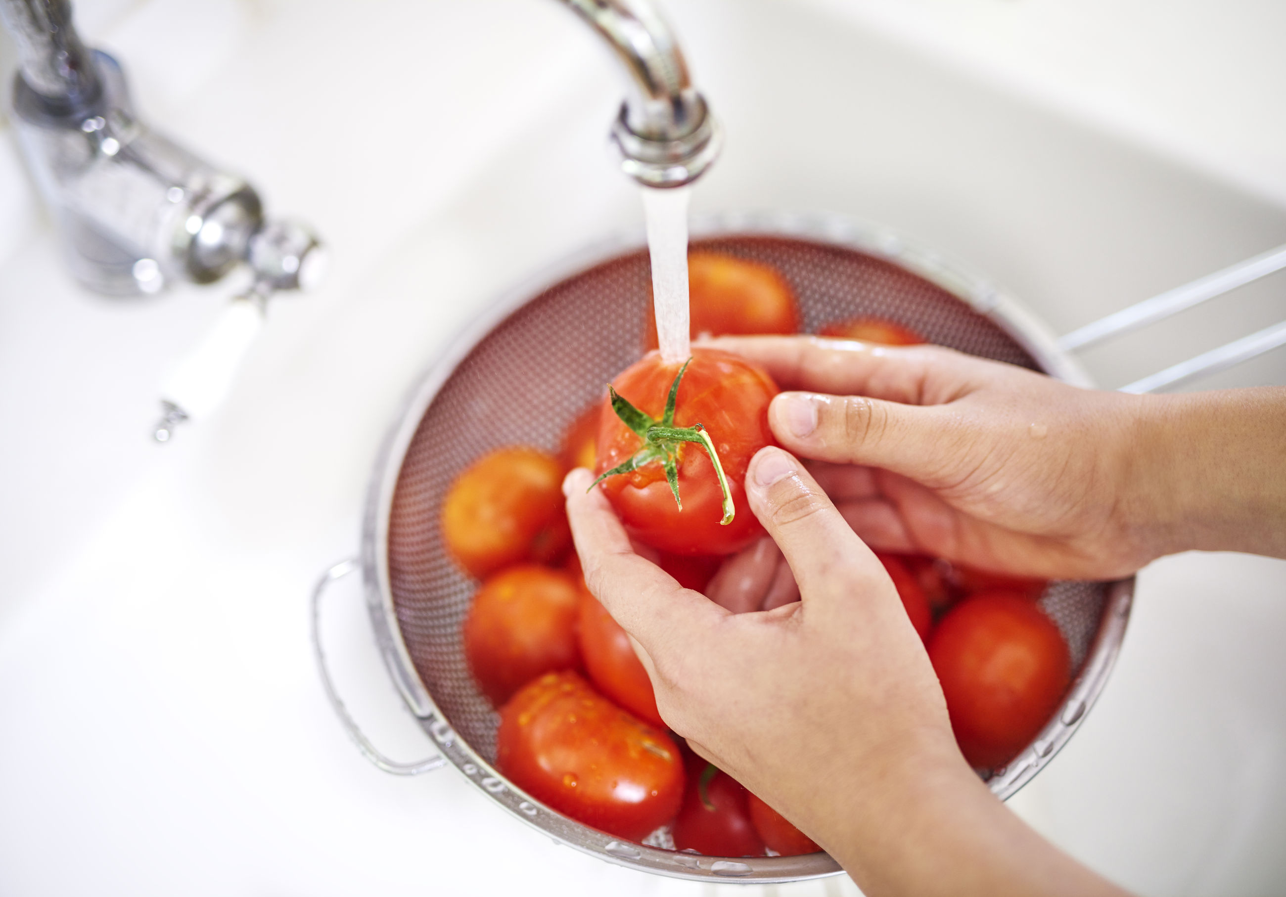 Cropped hands of teenage girl washing tomatoes in sink at home