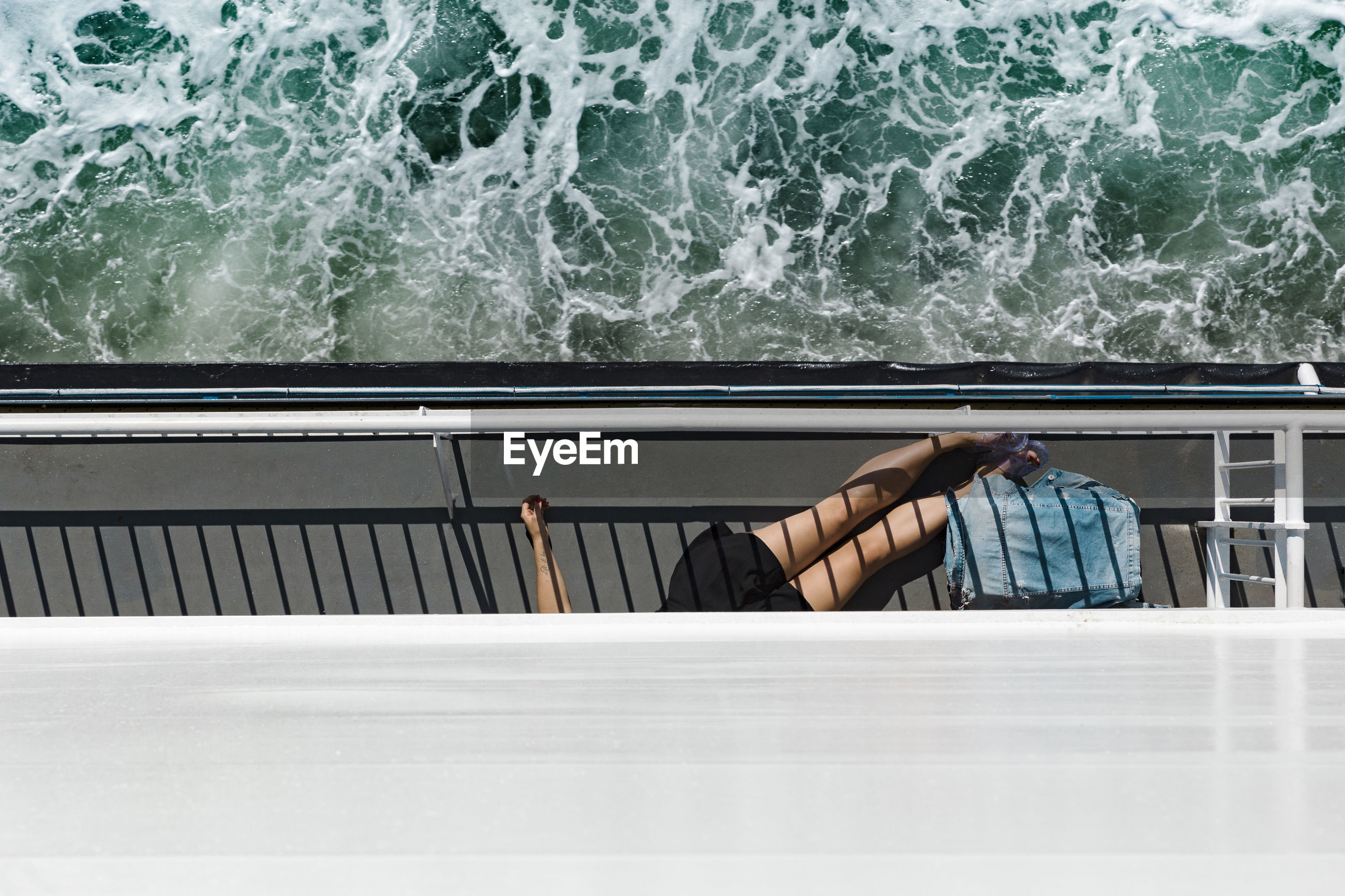 Low section of woman lying on boat at sea