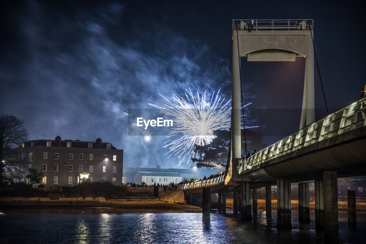 night, architecture, illuminated, built structure, water, building exterior, motion, firework, sky, bridge, long exposure, river, city, connection, bridge - man made structure, celebration, exploding, nature, firework display, no people, outdoors, firework - man made object, sparks, light, luxury