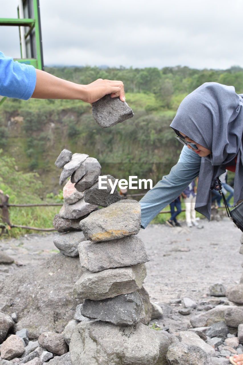 People stacking rocks against sky