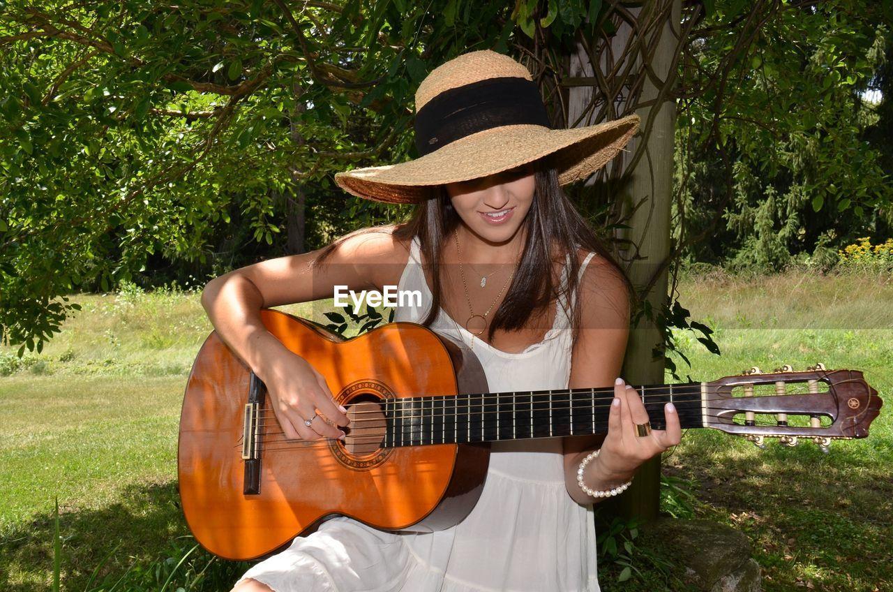 Beautiful woman playing guitar on field
