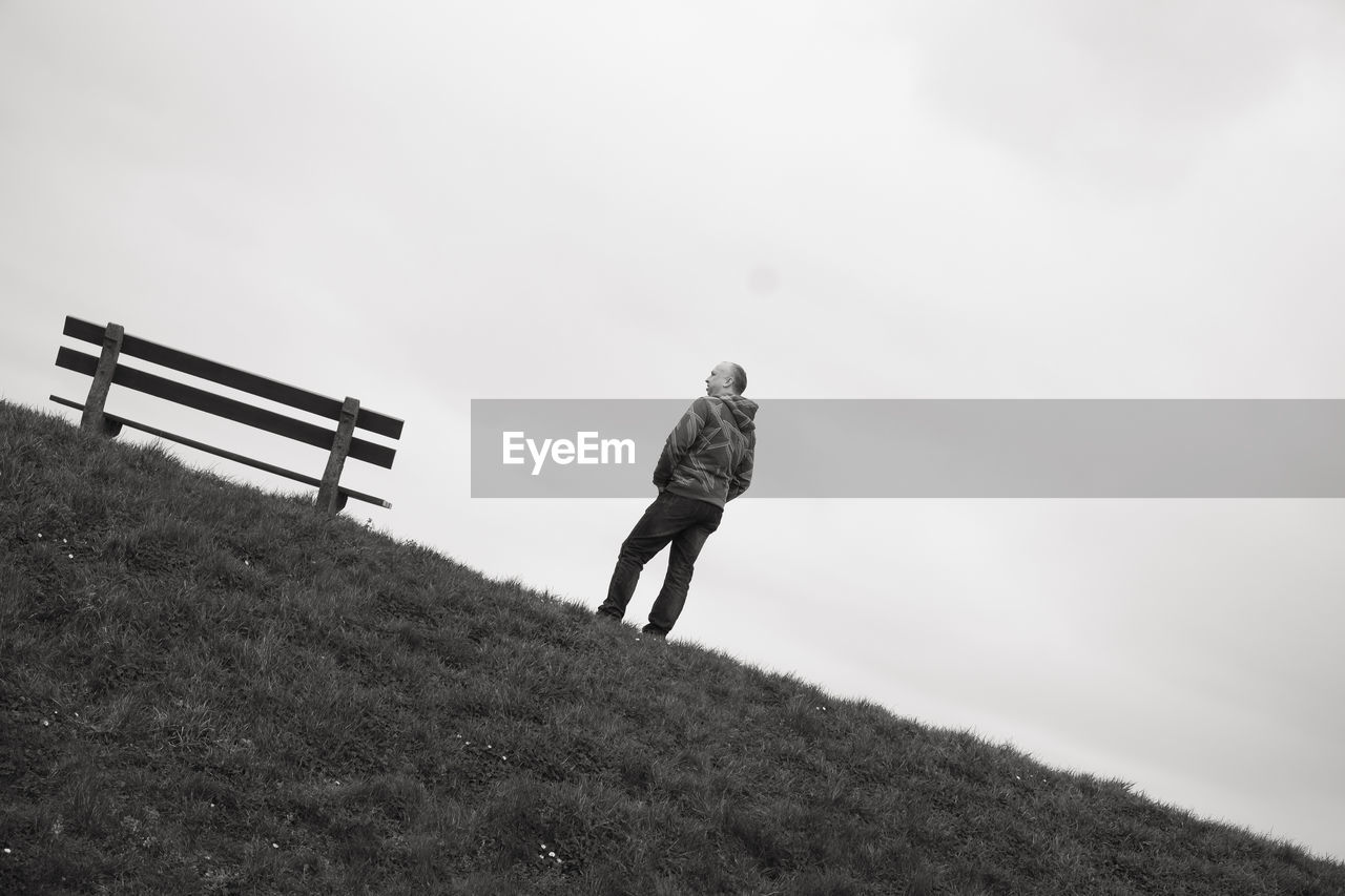 one person, real people, sky, full length, leisure activity, land, nature, lifestyles, day, rear view, field, walking, women, men, adult, casual clothing, standing, plant, outdoors, warm clothing