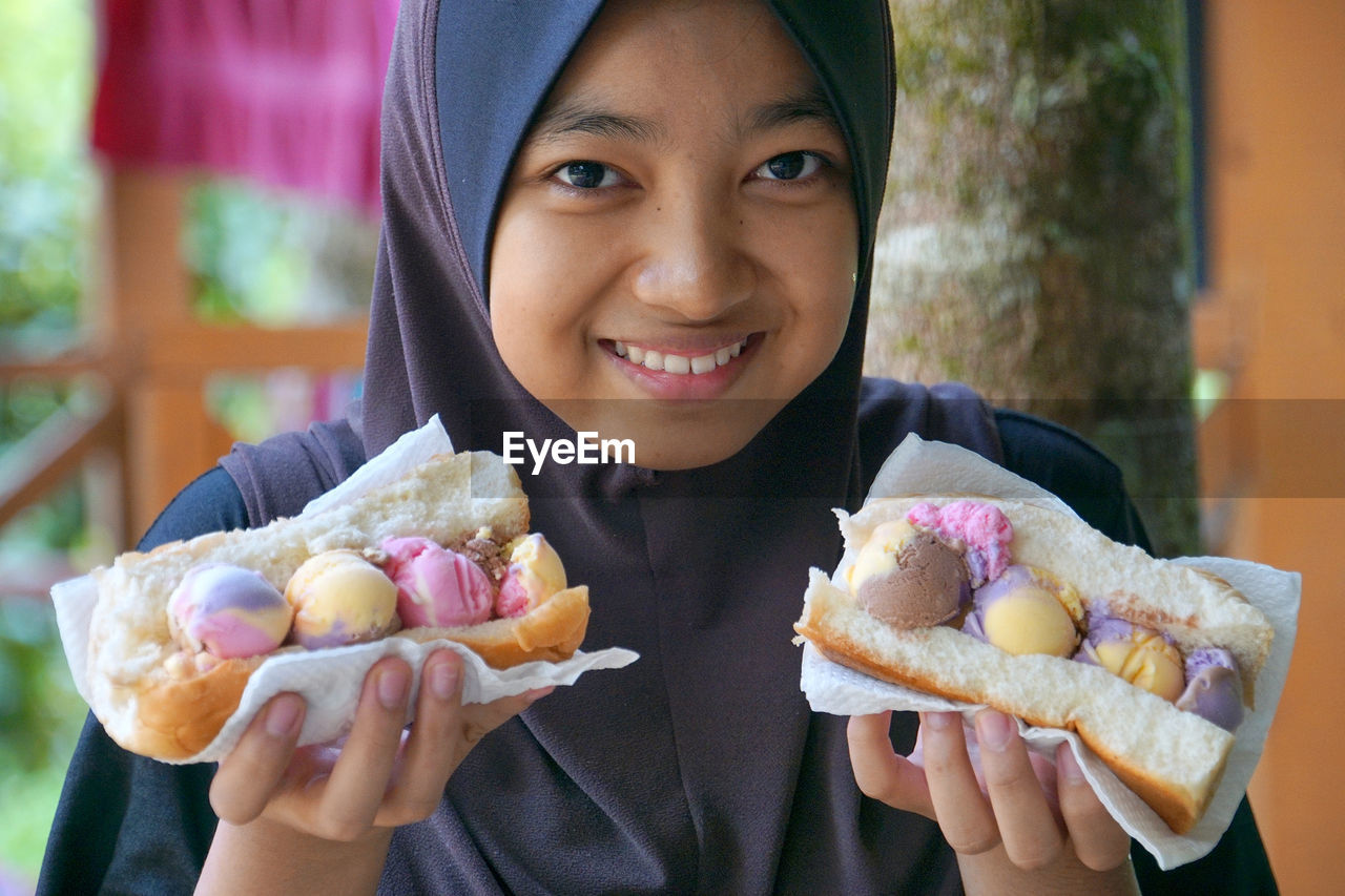 looking at camera, food and drink, real people, smiling, front view, one person, holding, portrait, food, unhealthy eating, focus on foreground, lifestyles, day, freshness, happiness, ready-to-eat, young women, sweet food, outdoors, young adult, close-up, people