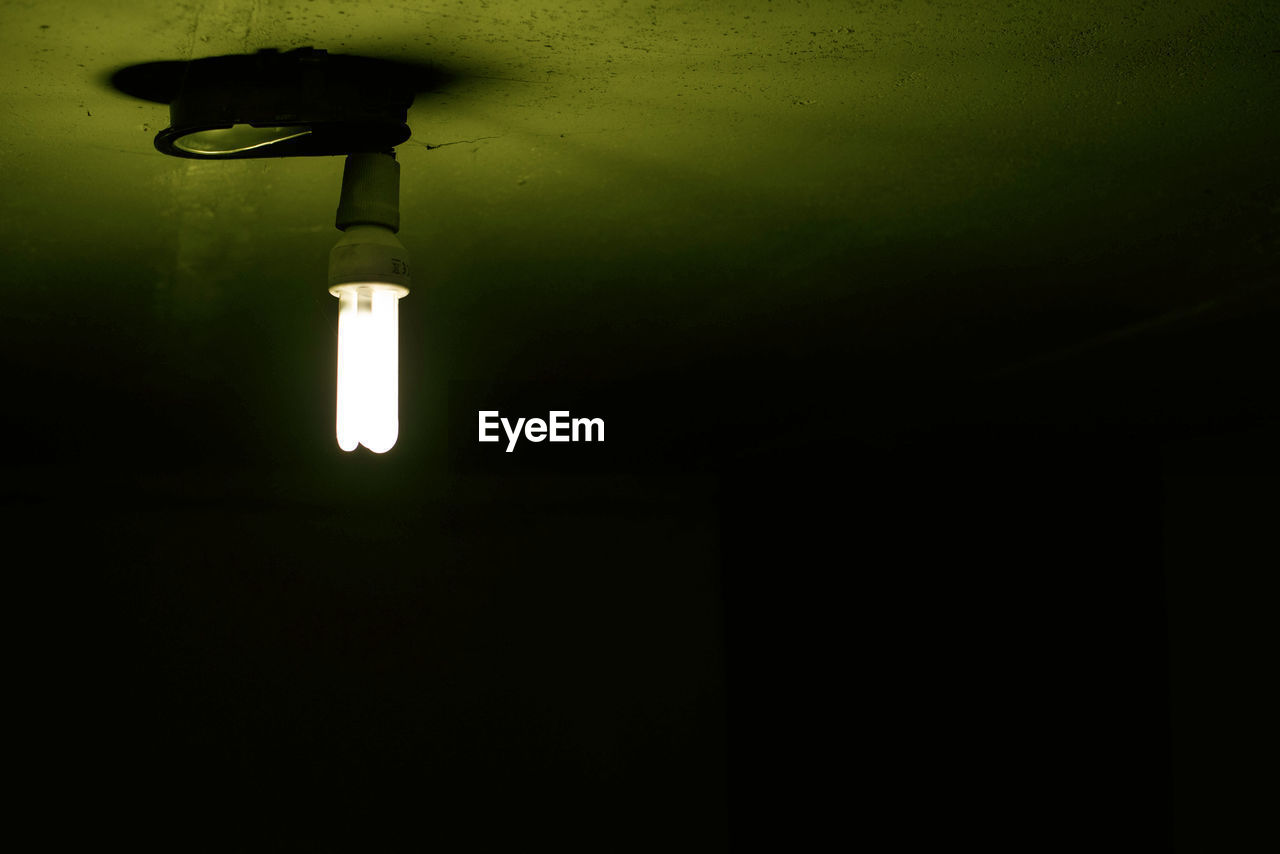 lighting equipment, electricity, illuminated, no people, light, low angle view, light bulb, dark, indoors, wall - building feature, glowing, night, electric light, copy space, electric lamp, technology, close-up, light - natural phenomenon, darkroom, energy efficient lightbulb, ceiling, electrical equipment, light fixture, black background, power supply