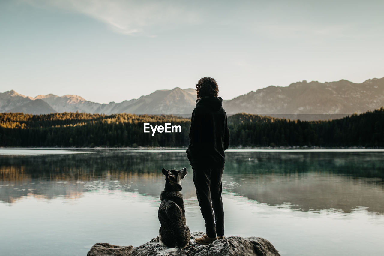Rear View Of Man With Dog Looking At Lake Against Mountain Range
