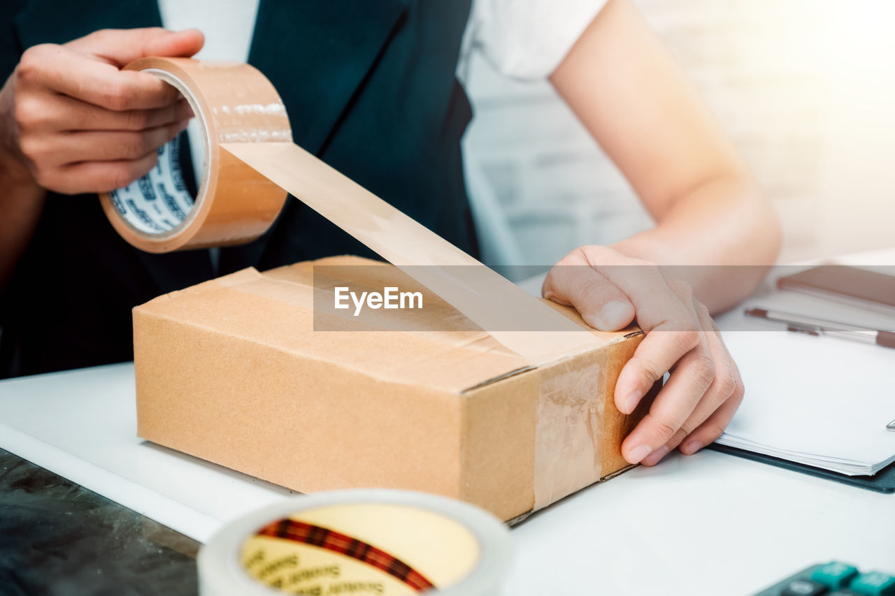 real people, table, one person, midsection, holding, indoors, front view, food and drink, men, business, box, occupation, food, selective focus, hand, focus on foreground, cardboard, box - container, human hand, take out food, tray