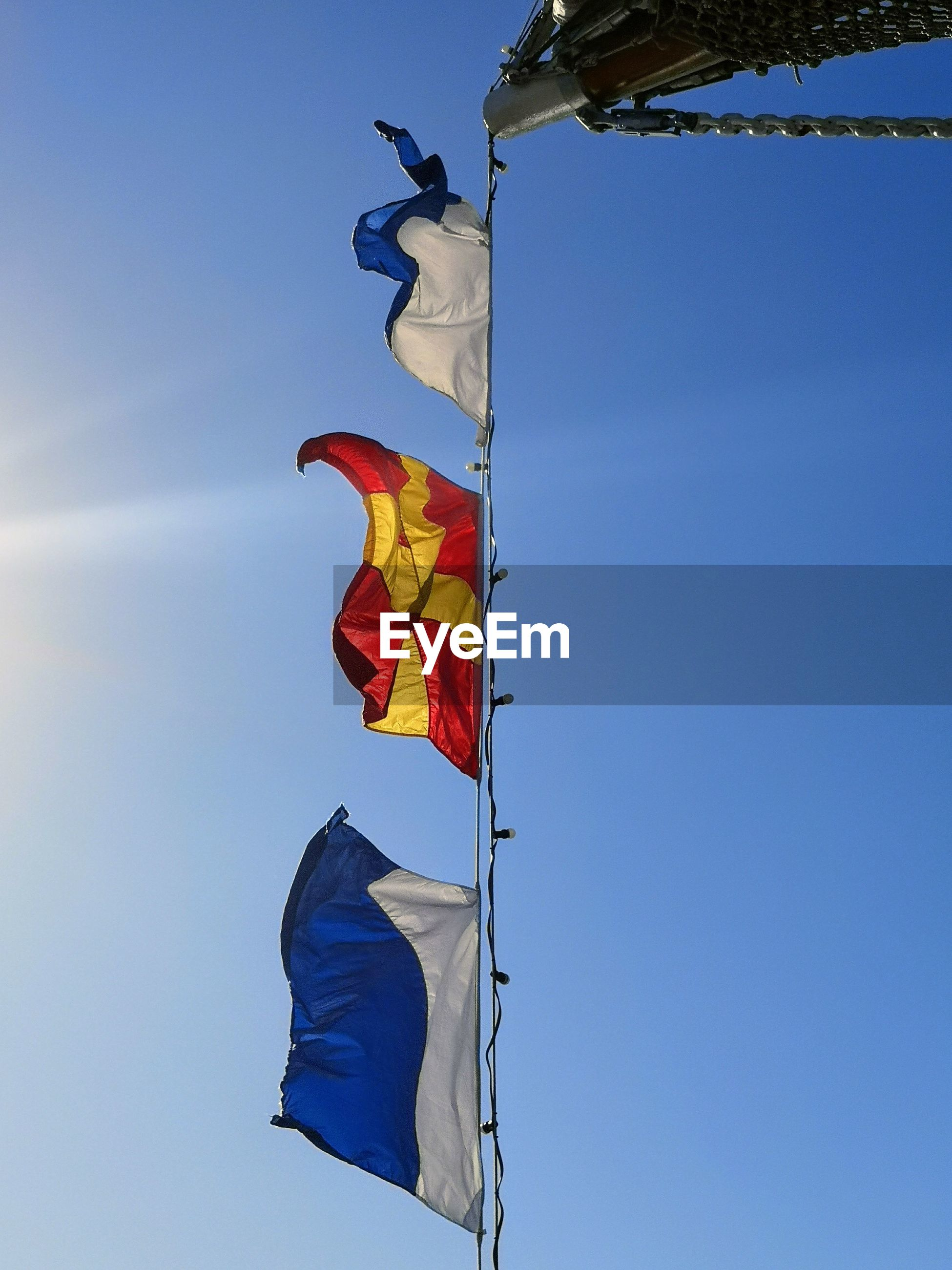 Low angle view of flag hanging against blue sky