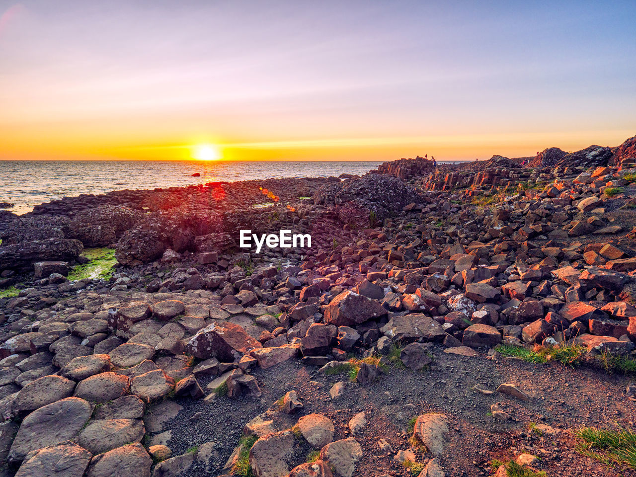 sky, sunset, rock, solid, scenics - nature, water, sea, rock - object, orange color, beauty in nature, sun, beach, land, nature, tranquil scene, tranquility, non-urban scene, no people, horizon, horizon over water, outdoors, pebble