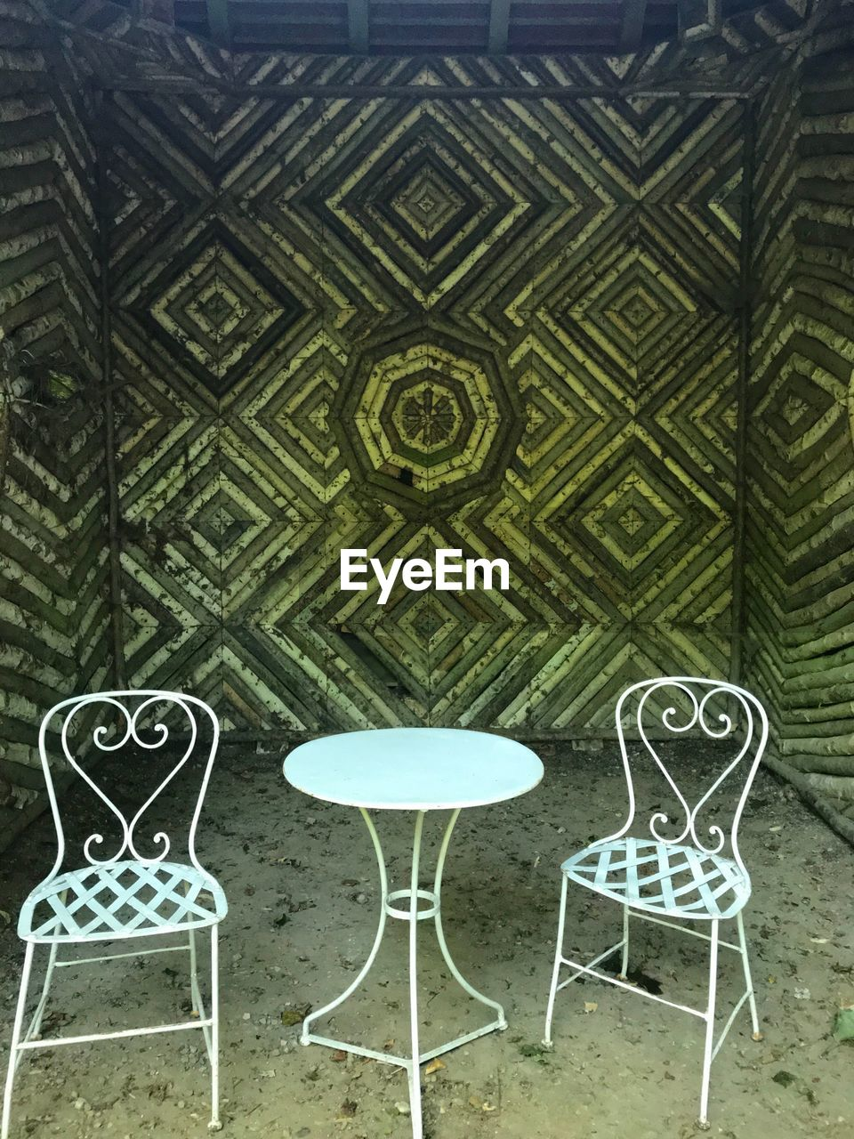 chair, seat, pattern, no people, absence, architecture, empty, built structure, green color, wall - building feature, design, table, day, indoors, art and craft, building, shape, metal, creativity, front or back yard, tiled floor