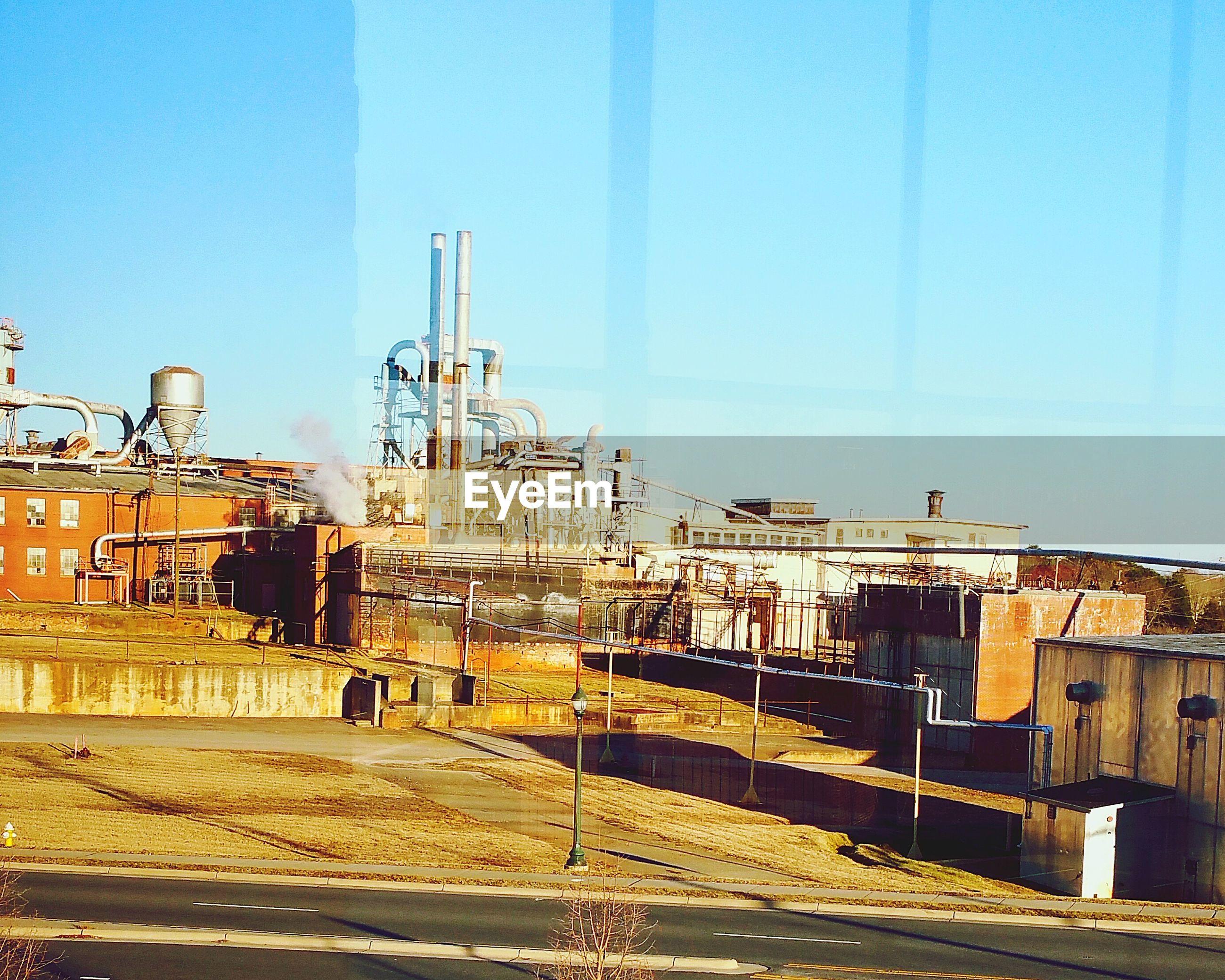 Industrial building against clear sky seen through window