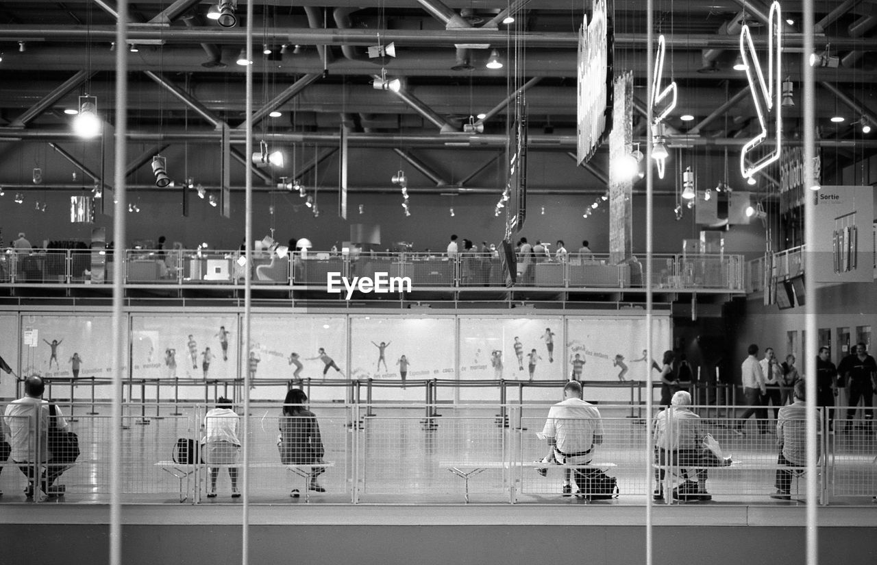 group of people, real people, illuminated, night, architecture, men, indoors, women, lifestyles, adult, glass - material, built structure, transportation, reflection, crowd, large group of people, blurred motion, motion, city, flooring, modern, waiting