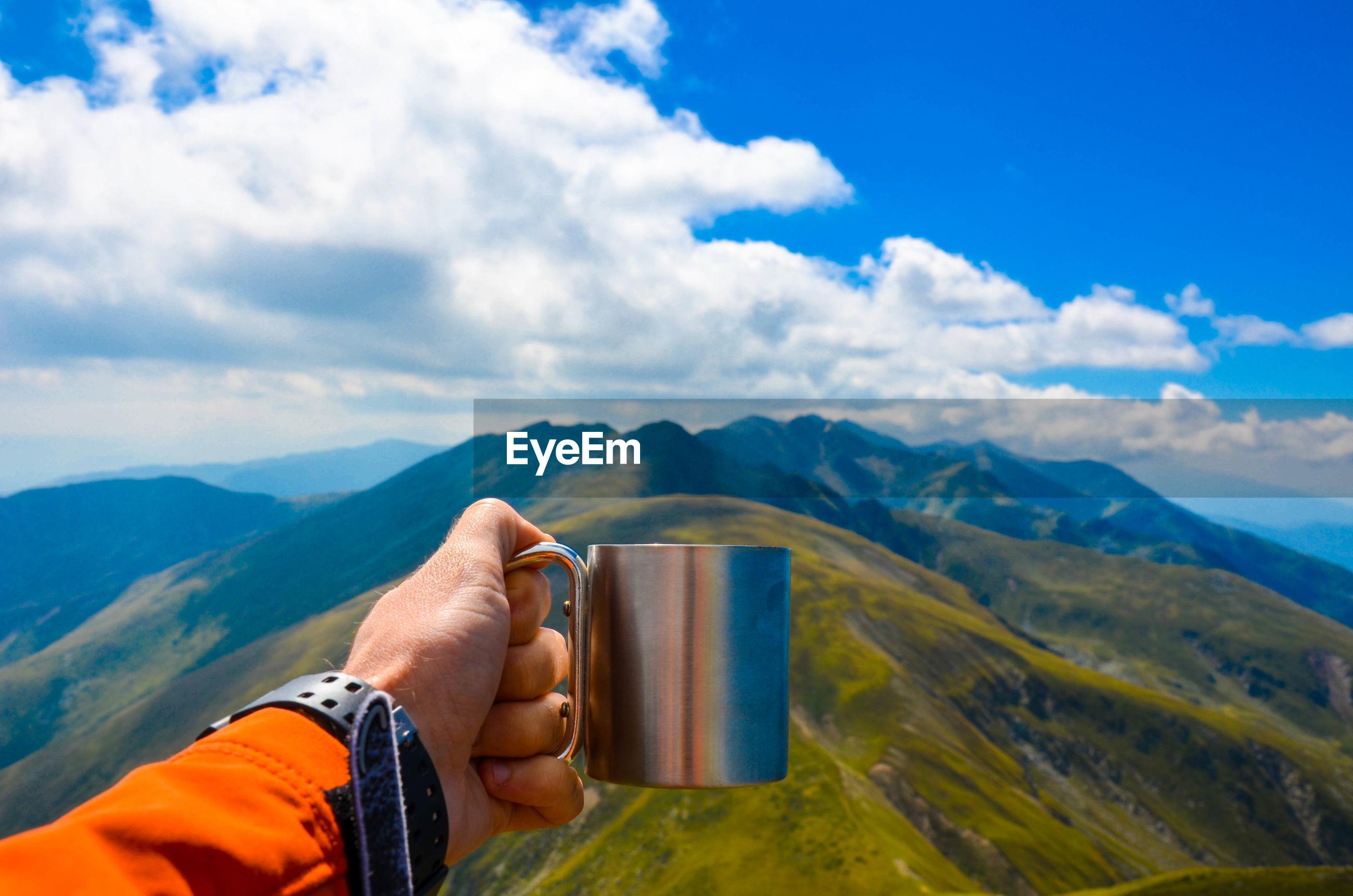 Cropped image of hand holding mug towards mountain range against sky