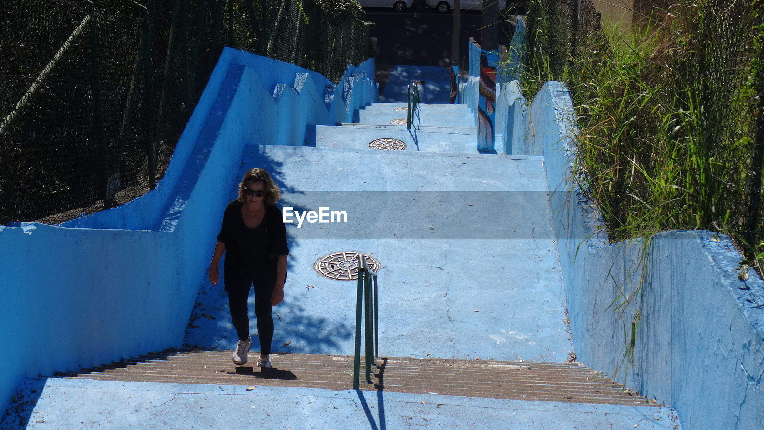 High angle view of woman climbing blue steps on sunny day
