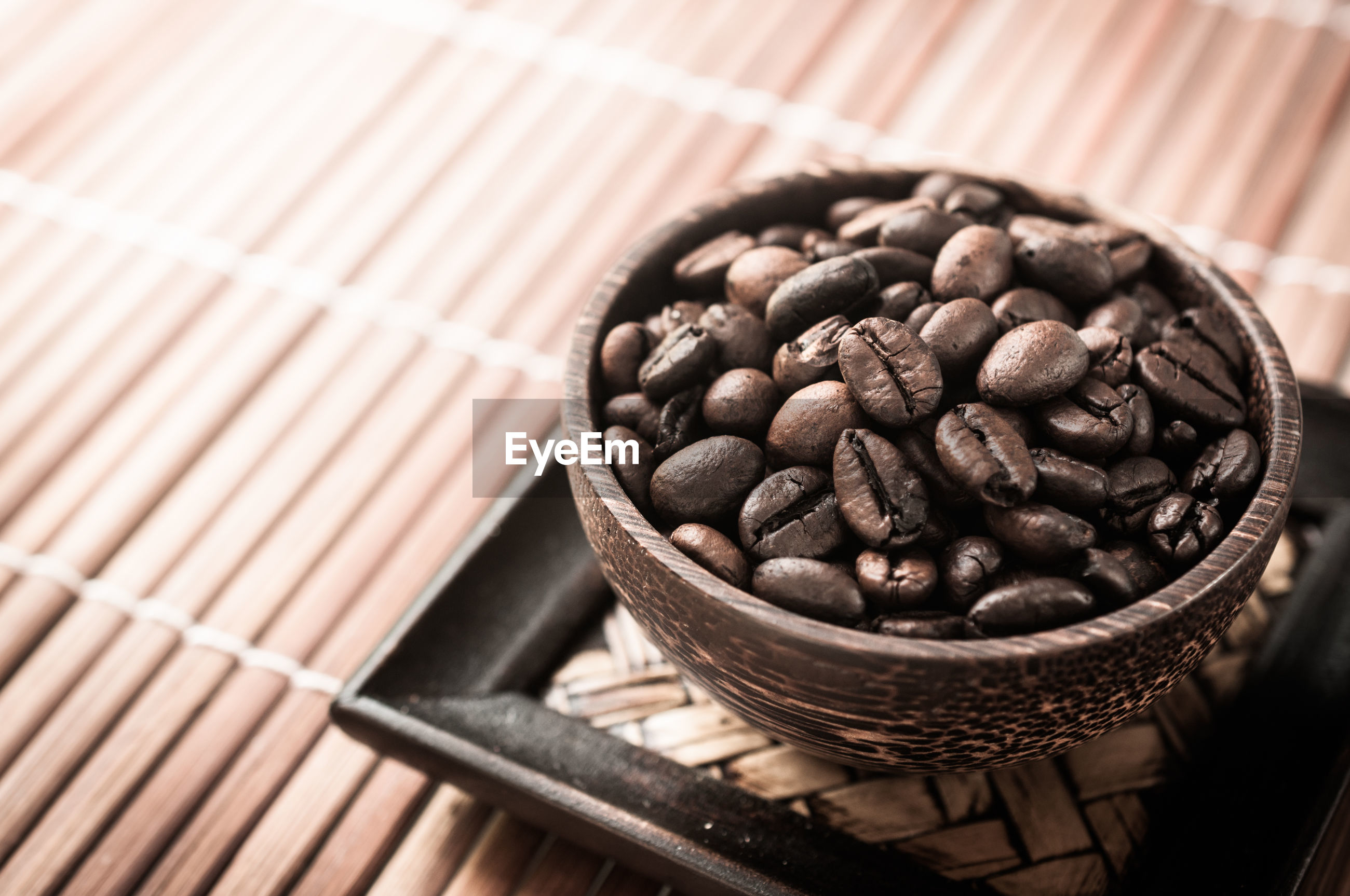 Close-up of roasted coffee beans in bowl on placemat