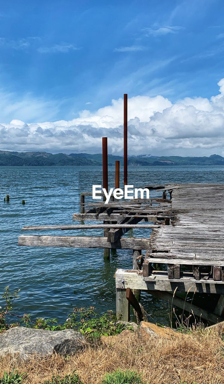 water, sea, sky, cloud - sky, day, nature, beauty in nature, land, no people, wood - material, tranquil scene, beach, scenics - nature, horizon, horizon over water, tranquility, outdoors, metal, architecture, post, wooden post