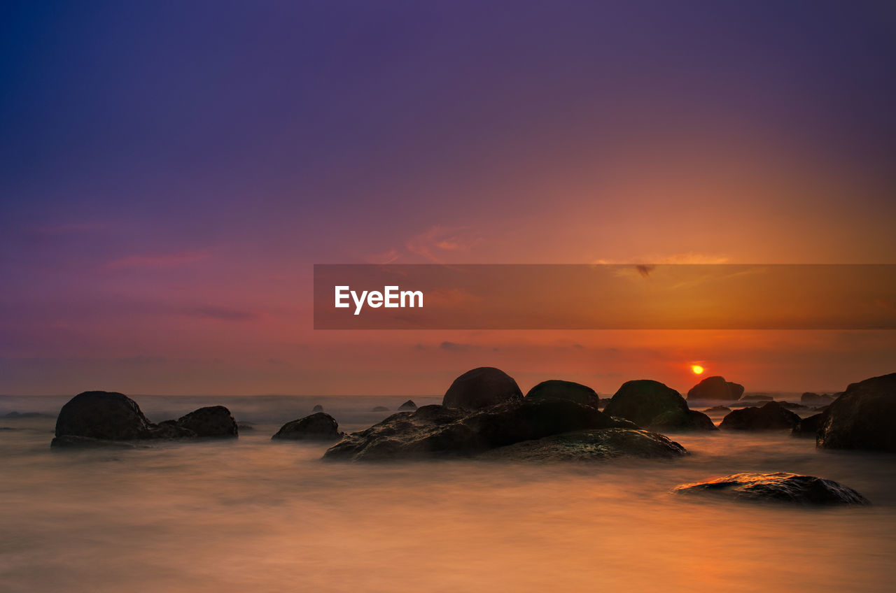 sky, sunset, scenics - nature, beauty in nature, rock, orange color, water, rock - object, tranquil scene, tranquility, solid, no people, idyllic, sea, cloud - sky, nature, waterfront, outdoors, long exposure, romantic sky