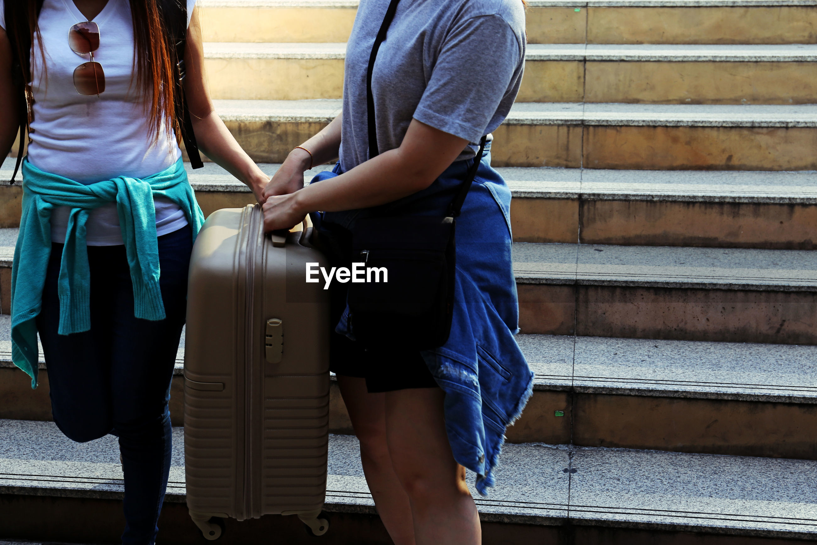 Midsection of women with luggage on steps