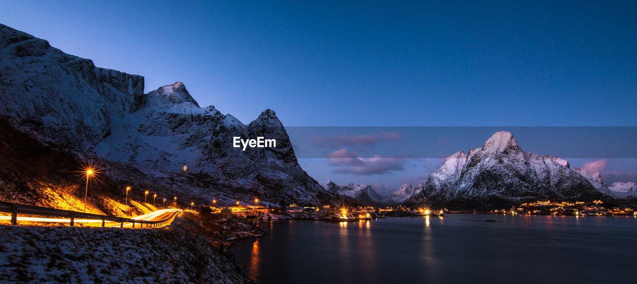 Scenic View Of Lake And Mountains Against Blue Sky At Night