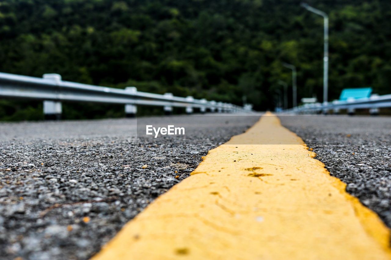 transportation, road, sign, diminishing perspective, selective focus, yellow, no people, road marking, marking, direction, the way forward, asphalt, symbol, day, street, surface level, nature, car, outdoors, close-up, dividing line