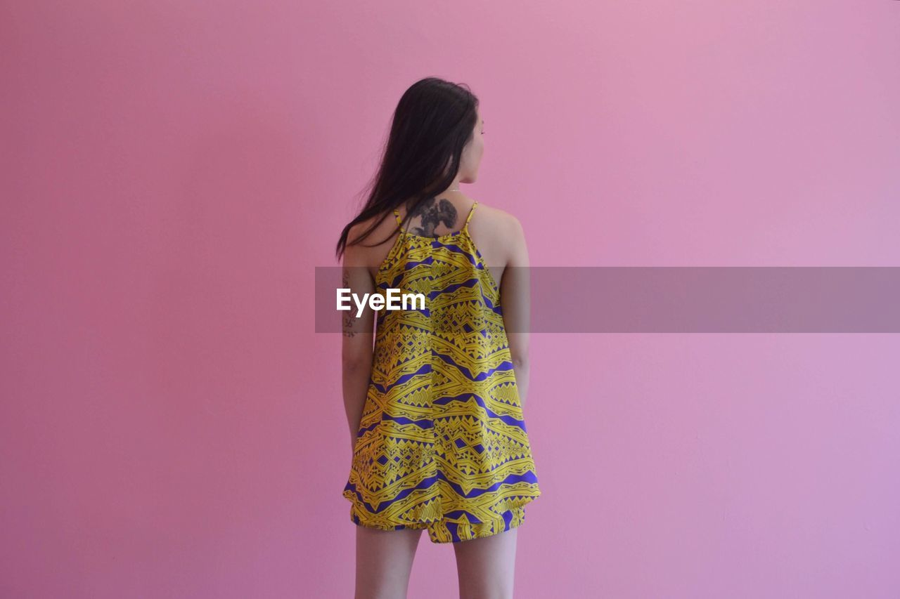 Rear View Of Woman Standing Against Pink Wall