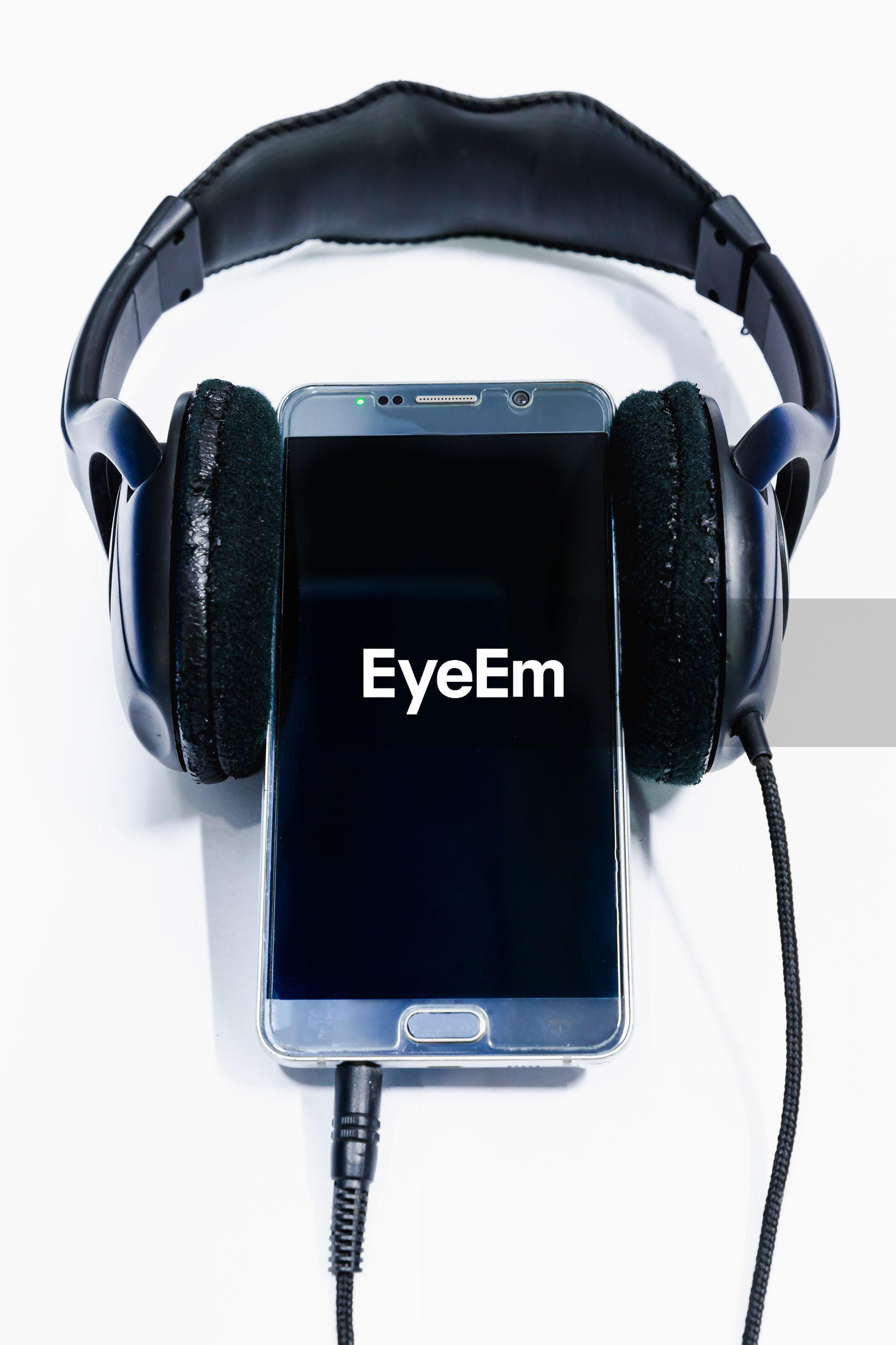 Close-up of smart phone and headphones against white background